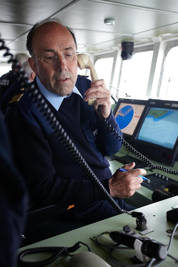Neustadt in Holstein, Lübecker Bucht, Ostsee. 7.5.2010 --  Küstenwache im Einsatz auf der Ostsee. Die Bundespolizei ist ein Teil der deutschen Küstenwache. Das Wachboot NEUSTRELITZ der Bundespolizei lauft bei schlechtem Wetter und Windstarke 8 zu einer Routinefahrt in die Lübecker Bucht aus. Schon nach wenigen Minuten sichtet die Mannschaft ein unbemannt im Wasser treibendes Surfbrett. Kommandant Peter Gau koordiniert von der Brücke aus eine Suchaktion nach dem vermissten Surfer. Mehrere Schiffe und das Martitime Rescue Coordination Center müssen informiert und in eine systematische Suchaktion eingebunden werden.