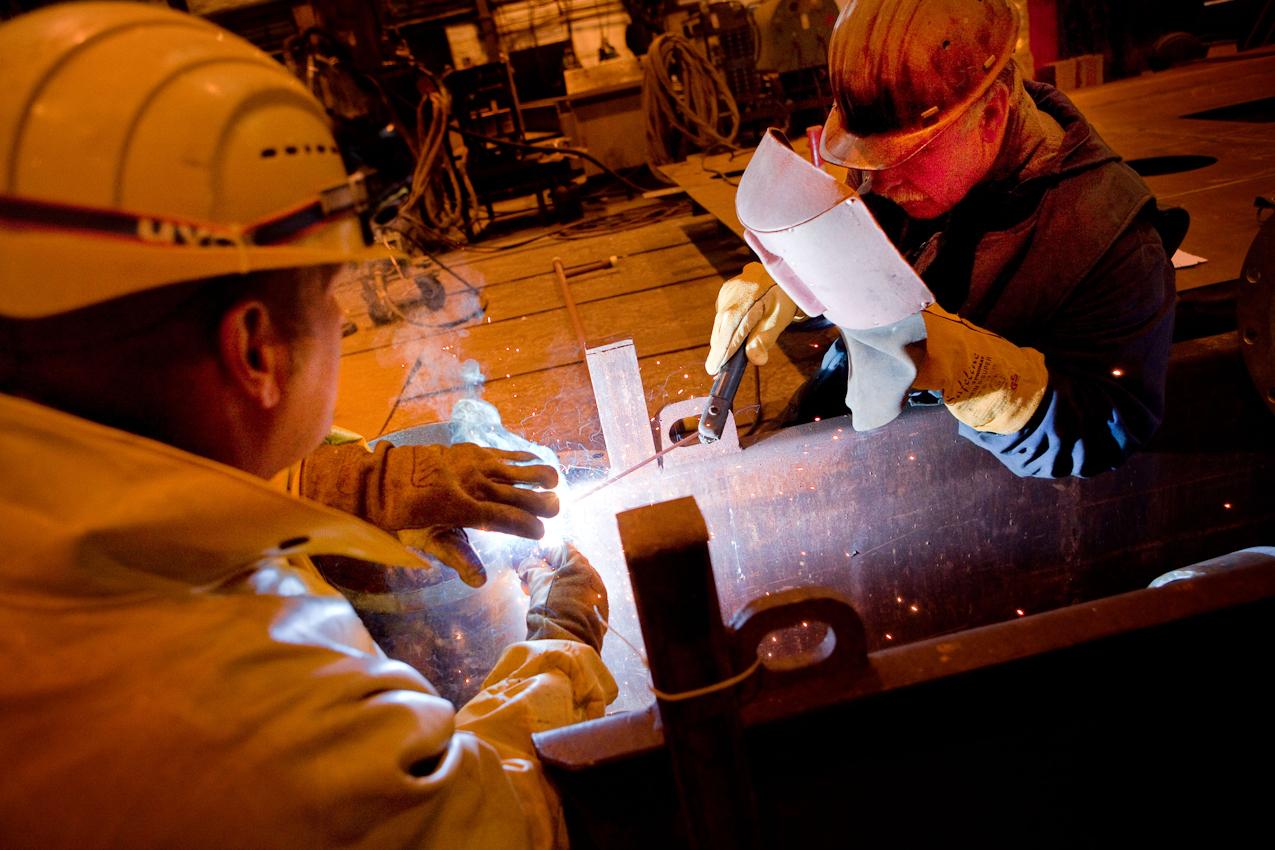 """Auf der Traditionswerft """"Flensburger Schiffbau-Gesellschaft"""" wurden seit 1872 uber 700 Schiffe gebaut. Die Werft ist mittlerweile eine der produktivsten Werften in Deutschland und hat sich auf den Bau von RoRo-Schiffen spezialisiert. Zwei Arbeiter schweißen einzelne Rohre in der Vorfertigung."""