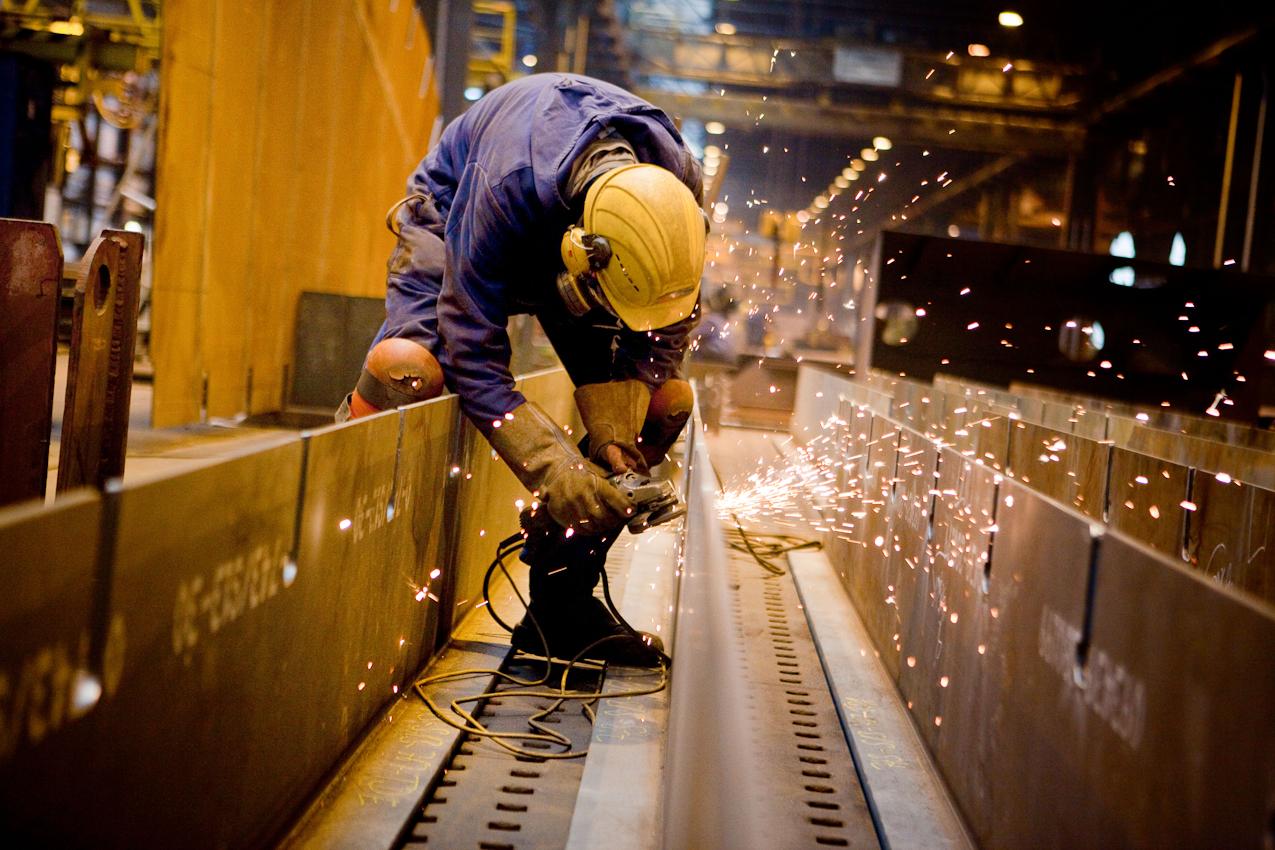 """Auf der Traditionswerft """"Flensburger Schiffbau-Gesellschaft"""" wurden seit 1872 uber 700 Schiffe gebaut. Die Werft ist mittlerweile eine der produktivsten Werften in Deutschland und hat sich auf den Bau von RoRo-Schiffen spezialisiert. Es sprühen die Funken als ein Werftarbeiter mit der Flex einzelne Stahlelemente des Schiffsrumpfes schleift."""
