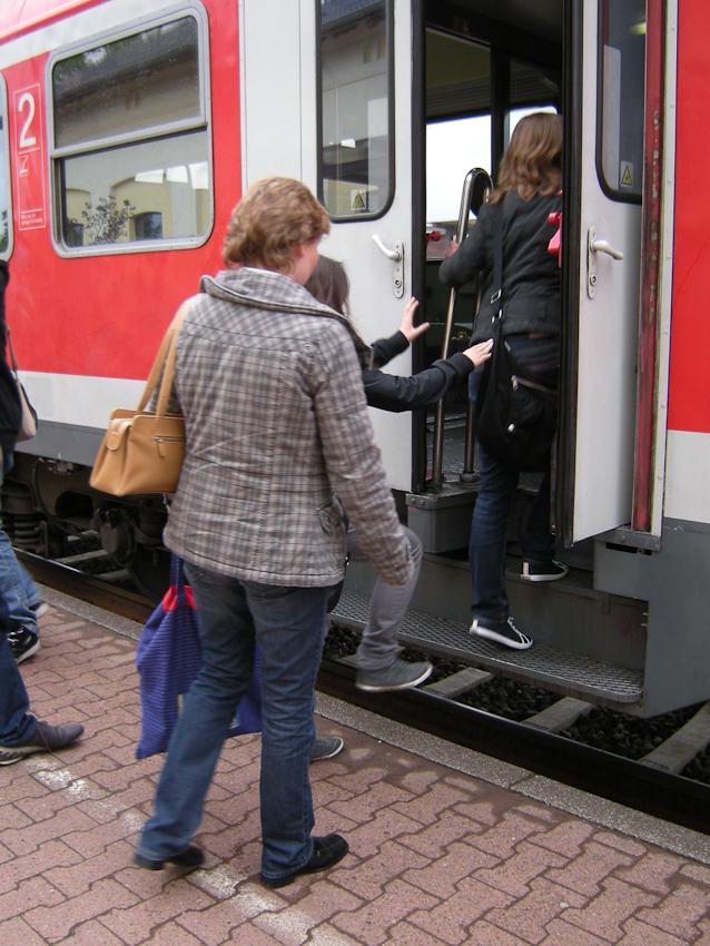 Menschen am Bahnhof Greven, dertäglich von ca. 2.000 Pendlern nach Münster / Westf. genutzt wird, aber bis heuet niedrige Bahnsteigkanten hat, so dass die Fahrgäste beim Ein- und Aussteiegen klettern nmüssen.