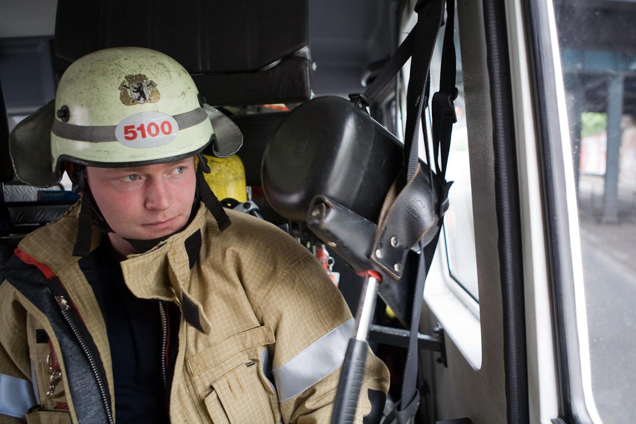 Ein Feuerwehrmann der Feuerwache Neukölln im Löschfahrzeug auf dem Weg zu einem Einsatz.