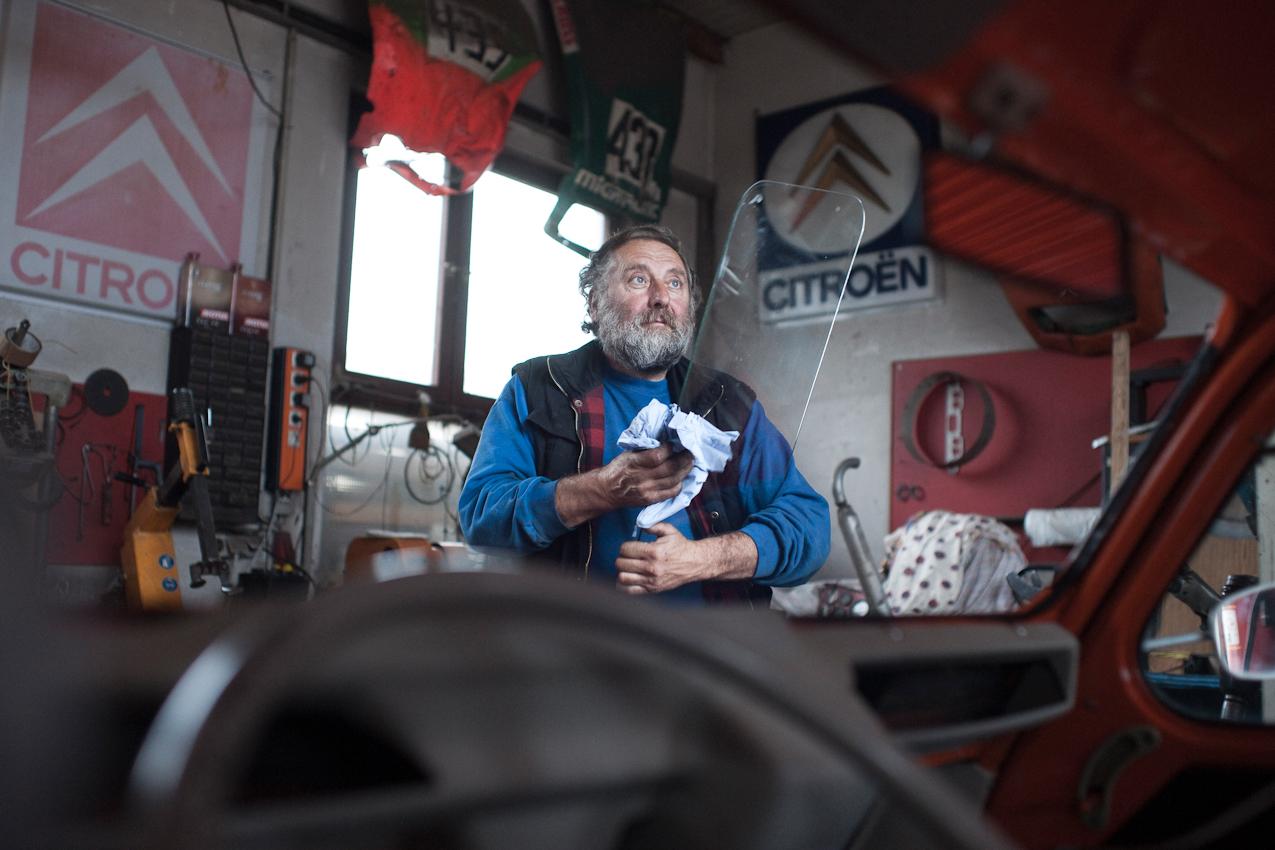 Das Foto entstand in der Auto-Werkstatt Franz Schreier 2CV Service+Teile in 74889 Sinsheim-Reihen, Baden-Wuerttemberg, Deutschland am 7. Mai 2010 um 18.05 Uhr. Zu sehen ist der Chef Franz Schreier beim Putzen einer Windschutzscheibe fur den Einbau bei einem Citroen 2CV. Im Hintergrund sieht man 2 beschaedigte Motorhauben von Renn-2CVs haengen. Das Foto entstand aus dem Innenraum des zu reparierenden 2CVs.