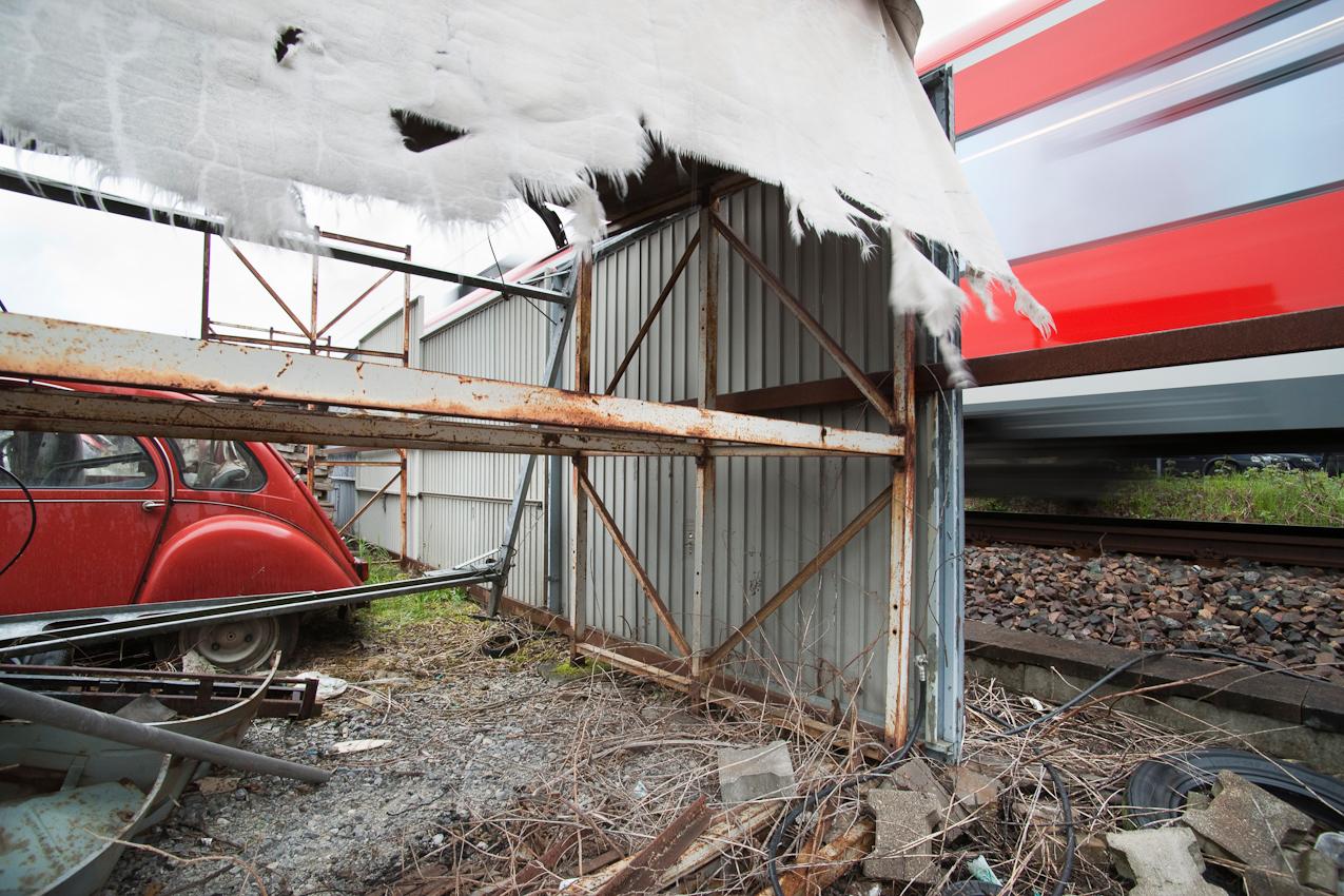 Das Foto entstand auf dem Gelaende der Auto-Werkstatt Franz Schreier 2CV Service+Teile in 74889 Sinsheim-Reihen, Baden-Wuerttemberg, Deutschland am 7. Mai 2010 um 15.43 Uhr. Zu sehen ist ein alter Citroen 2CV, Schrott und ein vorbeifahrender Zug.