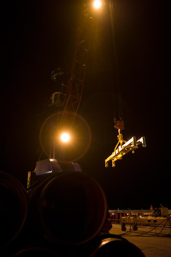 EUPEC PipeCoatings France SA ist Vertragspartner im Nord Stream Projekt zur Logistik und Betonummantelung der Stahlrohre für beide der je 1.220 km langen Ostseepipelines, die in Mukarn auf der Insel Rügen von ca. 300 Arbeitern produziert werden. Die Rohre werden rund um die Uhr je nach Geschwindigkeit der Verlegeschiffe per Kran, in dieser Nacht bei annähernd Windstarke 10, auf das Transportschiff verladen.