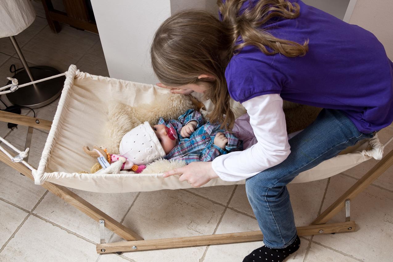 Luca schauckelt ihre Schwester Cara in den Schlaf