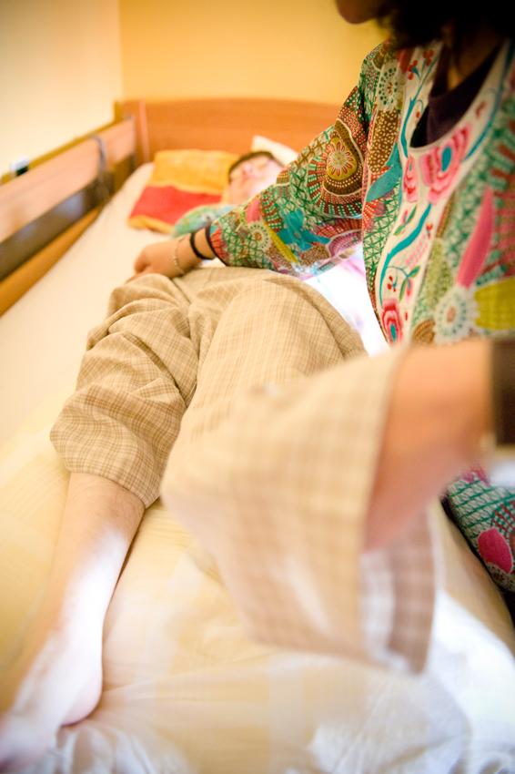 Nicole Spiegel ist eine Bewohnerin des Jakob-Riedinger-Hauses in Würzburg, einem Wohn- und Wohnpflegeheim für Menschen mit Behinderung. Der Bezirk Unterfranken hat sich die psychiatrische und neurologische Versorgung der unterfränkischen Bevölkerung zur wichtigsten gesundheitspolitischen Aufgabe gemacht. Sie zeigt, wie sie in ihren Tag startet. Eine Physiotherapeutin hilft Nicole beim Anziehen.