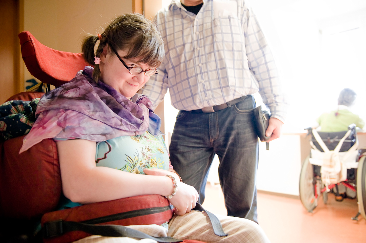 Nicole Spiegel ist eine Bewohnerin des Jakob-Riedinger-Hauses in Würzburg, einem Wohn- und Wohnpflegeheim für Menschen mit Behinderung. Der Bezirk Unterfranken hat sich die psychiatrische und neurologische Versorgung der unterfränkischen Bevölkerung zur wichtigsten gesundheitspolitischen Aufgabe gemacht. Sie zeigt, wie sie in ihren Tag startet. Nicole wartet in ihrem Zweibettzimmer auf eine Massage.
