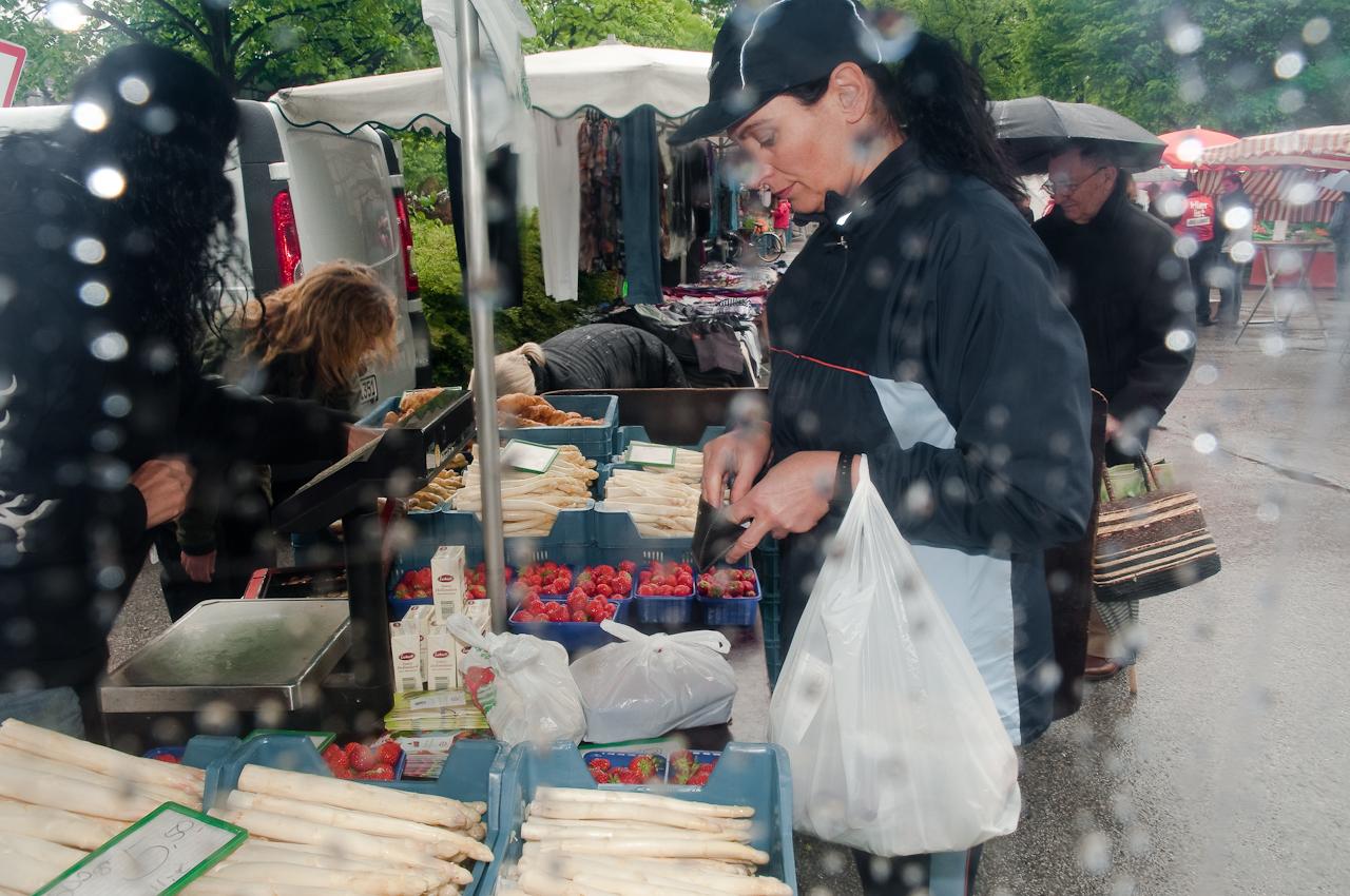 Wochen-Markttag am 7.5.2010 in Refrath, Bergisch Gladbach, fotografiert von Ulla Franke. Frau Kamm steht am Spargelstand und schaut in ihr Portemonaie, um ihren Einkauf zu bezahlen. Es sind Regentropfen im Vordergrund zu sehen.