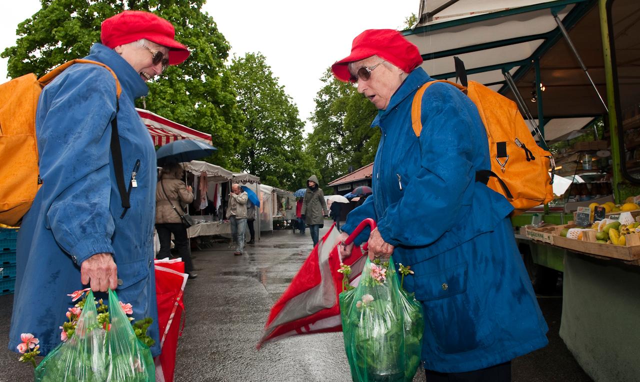 Wochen-Markttag am 7.5.2010 in Refrath, Bergisch Gladbach, fotografiert von Ulla Franke. Zwei Damen, die identisch gekleideten Thomes Zwillinge, stellen soeben fest, dass sie, jede für sich, auch noch die gleichen Pflanzen gekauft haben. daruber amüsieren sie sich. Im Hintergrund sieht man nassen Asphalt und eine Wochen-Marktszene.