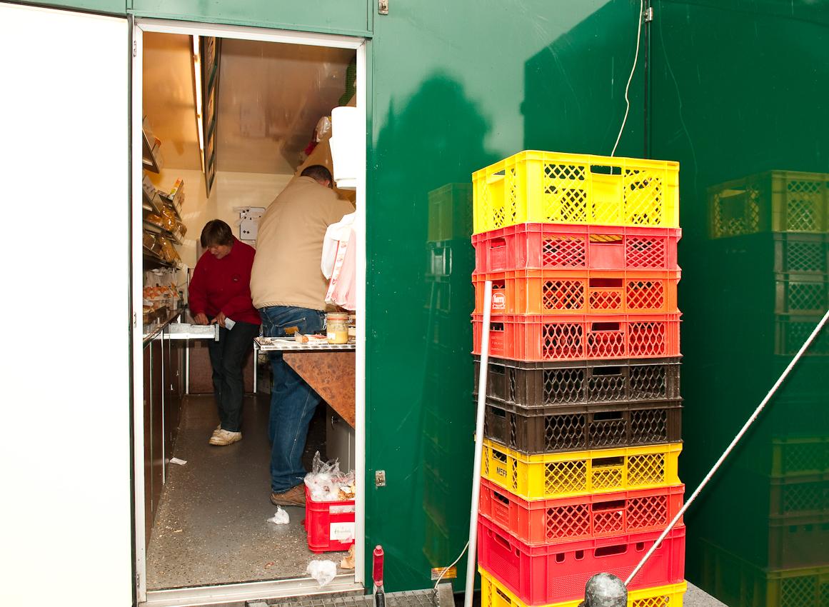 Wochen-Markttag in Refrath, Bergisch Gladbach, am 7.5.2010, fotografiert von Ulla Franke. Seitenansicht eines grunen Marktstandes. Durch die offene Türe sieht man Flemms bei der Verkaufstätigkeit. Rechts der Türe befinden sich gestapelte Kisten.