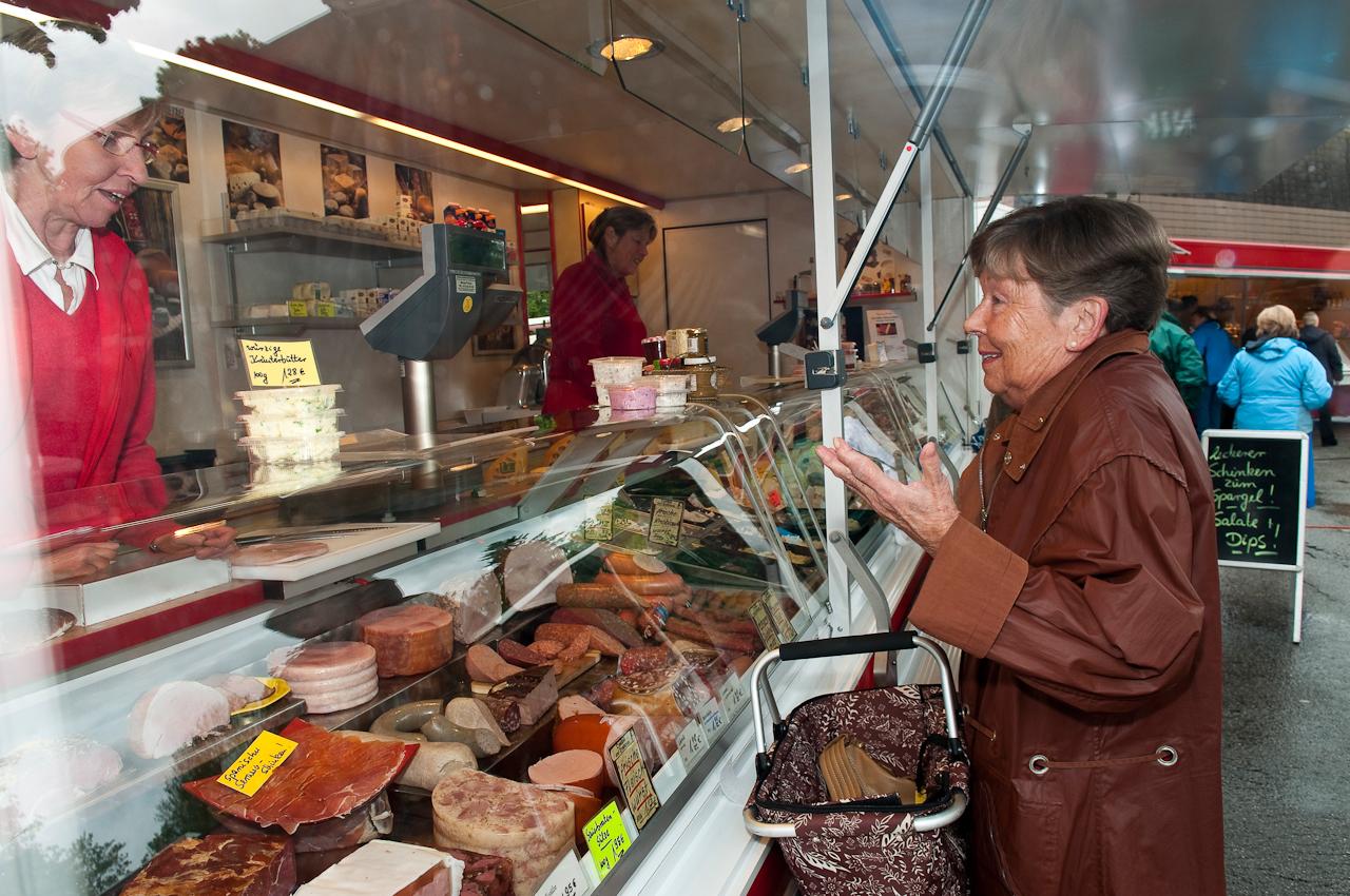 Wochen-Markttag in Refrath, Bergisch Gladbach, am 7.5.2010, fotografiert von Ulla Franke. Frau Gemunder unterhält sich über den Verkaufstresen mit der Verkäuferin des Wurst-und Kasestandes, Frau Buchholz und deutet mit einer Geste an, dass man an dem Wetter nichts ändern kann. Beide sind zueinander gewandt.