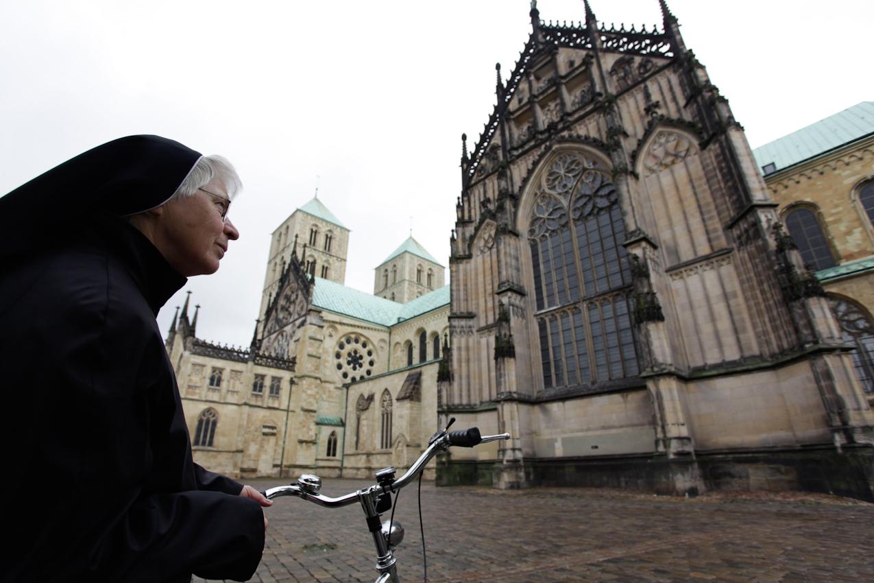 Schwester Bernharde vom Orden der Clemensschwestern mit ihrem Fahrrad auf dem Domplatz in Münster, Westfalen. Sie feiert im Herbst 2010 ihr 50-jähriges Ordensjubilaum und hat auch den grossten Teil ihres Lebens in Münster verbracht.