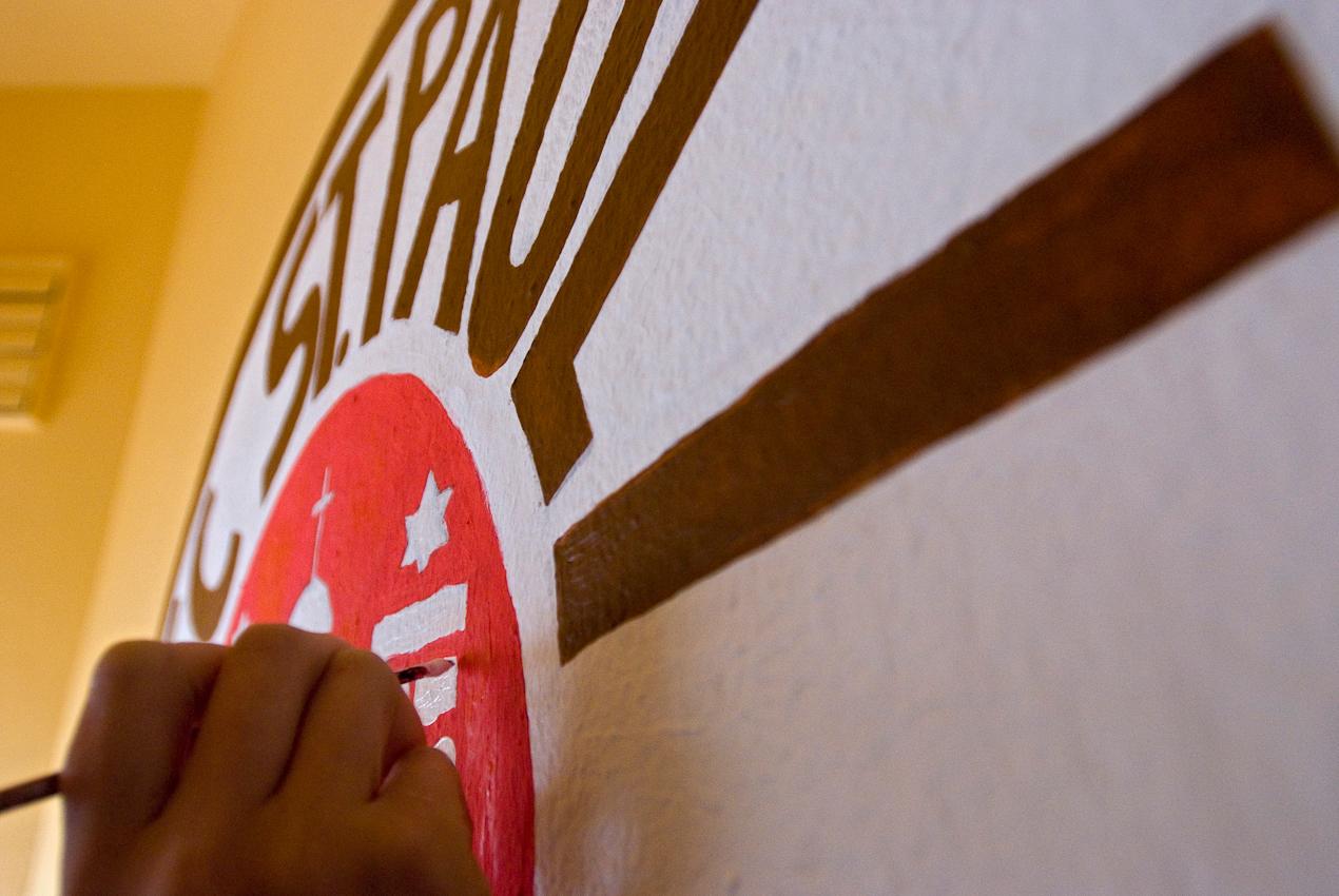 Die scheue, angehende Kunststudentin Marie-Luisa vollendet am Nachmittag des 7. Mai mit viel Liebe zum Detail  ihre Wandmalerei des FC St. Pauli-Logos. Die Basiskneipe Tippel II, Seilerstr. Ecke Hain-Hoyer-Str., beauftragte sie den Eingangsbereich zur 100-Jahrfeier des Vereins mit dem Logo zu schmücken.