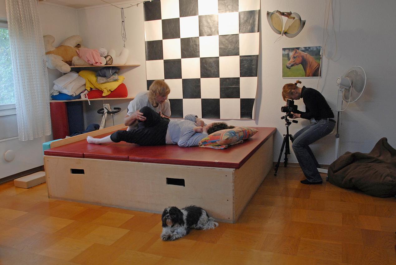 """<p>Making Off-Aufnahme über Selbstauslöser mit Fotografin Silke Kirchhoff und ihrer Rolleiflex-Kamera im Bild. """"Pusten heißt """"Nein"""", """"Ahh"""" heißt """"Ja""""!"""" Die seit 18 Jahren im Wachkoma lebende Svenja wird am 07.05.2010 von der Physiotherapeutin Kirsten Bejarano auf dem Podest in Svenjas Zimmer in Hannover behandelt. Rhythmisch-Tonischer-Dialog nennt sich diese Therapieform.</p>"""