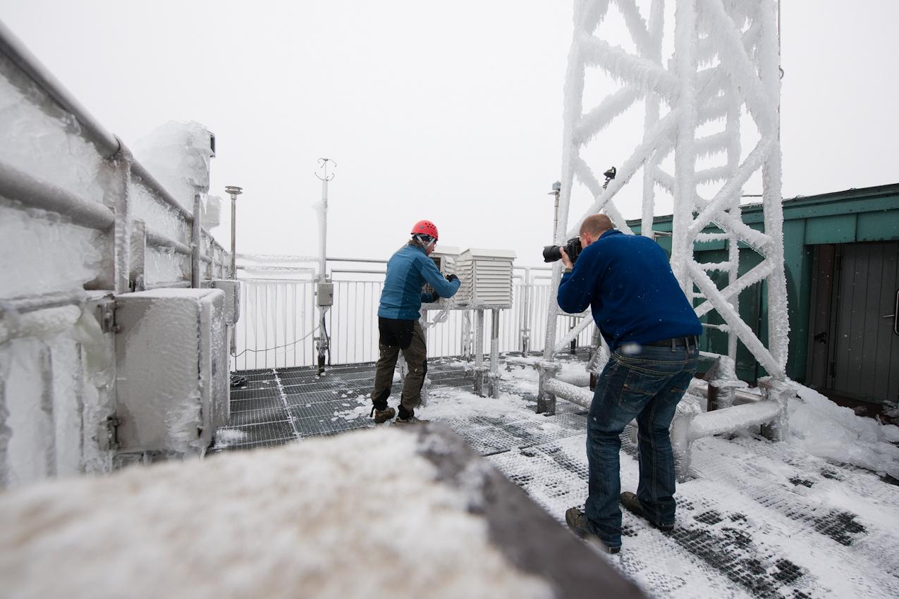 Wo kommt das Wetter her? - Ein Tag mit dem Wetterdiensttechniker Rene Sosna auf dem Brocken.  Der Fotograf Henning Kramer fotografiert den Wetterdiensttechniker Rene Sosna bei der Arbeit. Hier befreit er gerade einen Messkasten auf dem Dach der Wetterwarte von Eis, um die Messintrumente darin abzulesen.
