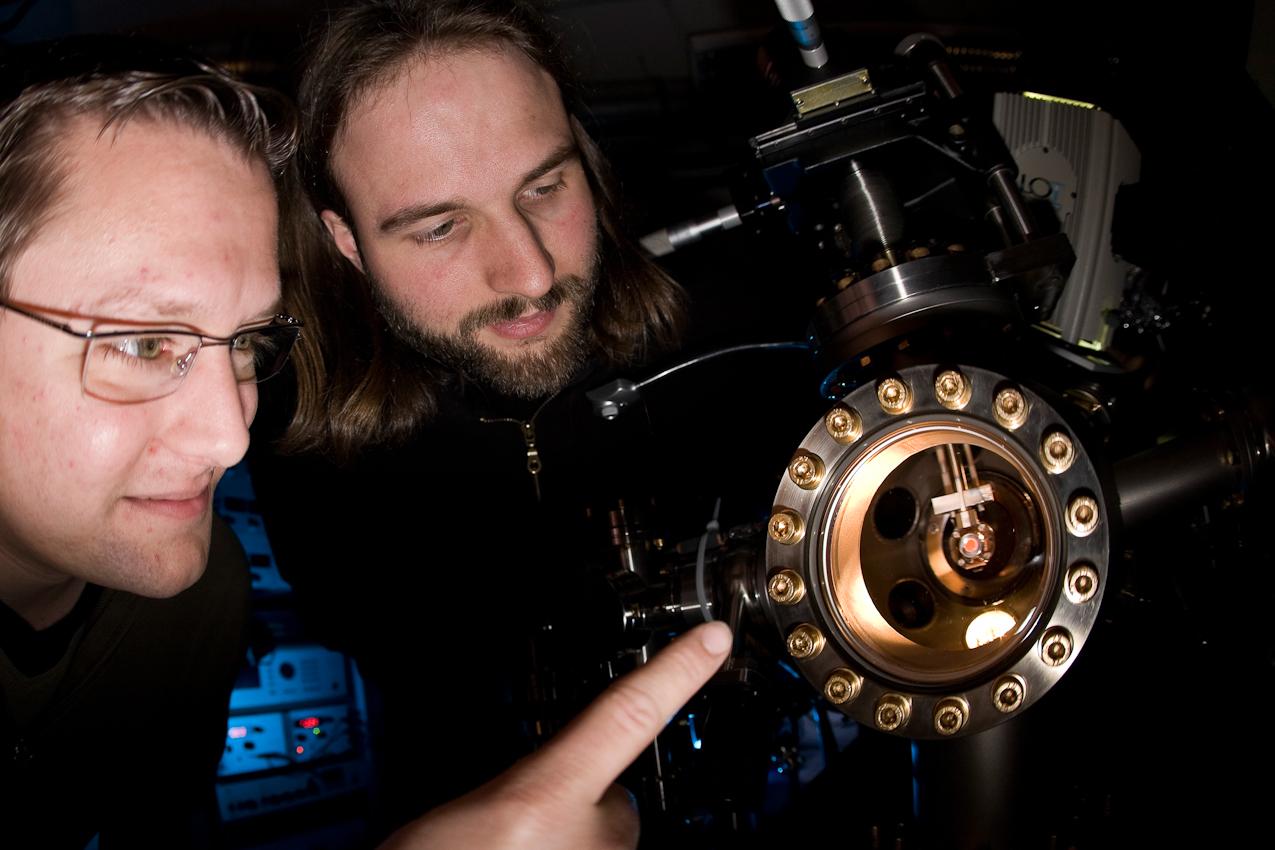 """7. Mai 2010: Universität Duisburg-Essen, Campus Duisburg, Fachbereich Physik:  Die Doktoranden Simon Sindermann (l.) und Jan Vanis betrachten eine glühende Iridium-Probe  in der Präparationskammer des PEEM (Photoelektronenemissionsmikroskop). Die Probe wurde auf die Kristallflache (111) geschnitten um Veränderungen im Nanobereich zu untersuchen, die mit Hilfe von Laserimpulsen angeregt wurden. Die Doktoranden gehören zur Arbeitsgruppe von Prof. Horn von Hoegen. Die Arbeitsgruppe wird von der Deutschen Forschungsgemeinschaft (DFG) im Sonderforschungsbereich 616 ,,Energiedissipation an Oberflächen"""" unterstützt."""