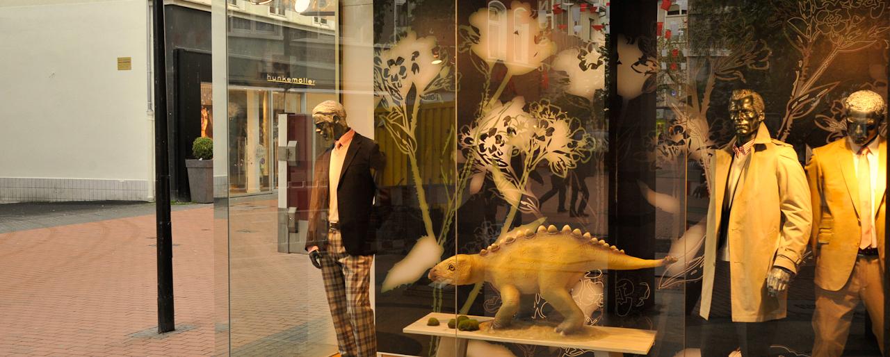 Dinosaurier in Gießen; Modelle und Spiegelungen von Menschen und Dinosauriern in Geschäften; die Stadt ist nach 19 Uhr fast ausgestorben