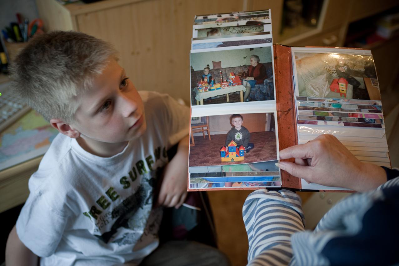 """Jan Phillips Oma zeigt Kinderbilder aus seinem Fotoalbum. Vieles ist ihm noch bekannt und vertraut. Nur an seine Mutter hat er keinerlei Erinnerungen. """"Die kann mich mal!"""" sagt er. -- Jan Phillip Biesecke (10 Jahre), der bei seinen Großeltern in Brandenburg/Havel lebt, geht jeden Tag nach der Schule in eine Tagesbetreuungsgruppe. Dort bekommt er Nachhilfe und verbringt mit anderen Kindern den Nachmittag. Jan Phillips Mutter hatte ihn mit 3 Jahren verlassen. Sein Vater, mit der Situation völlig überfordert, hatte ihn zu den Großeltern gegeben, bei denen er jetzt immer noch lebt. Die Tagesbetreuung wird vom Jugendamt finanziert und ist für Jan Phillips Großeltern eine Möglichkeit sich bei der Erziehung, die sie nur zum Teil leisten können, helfen zu lassen."""