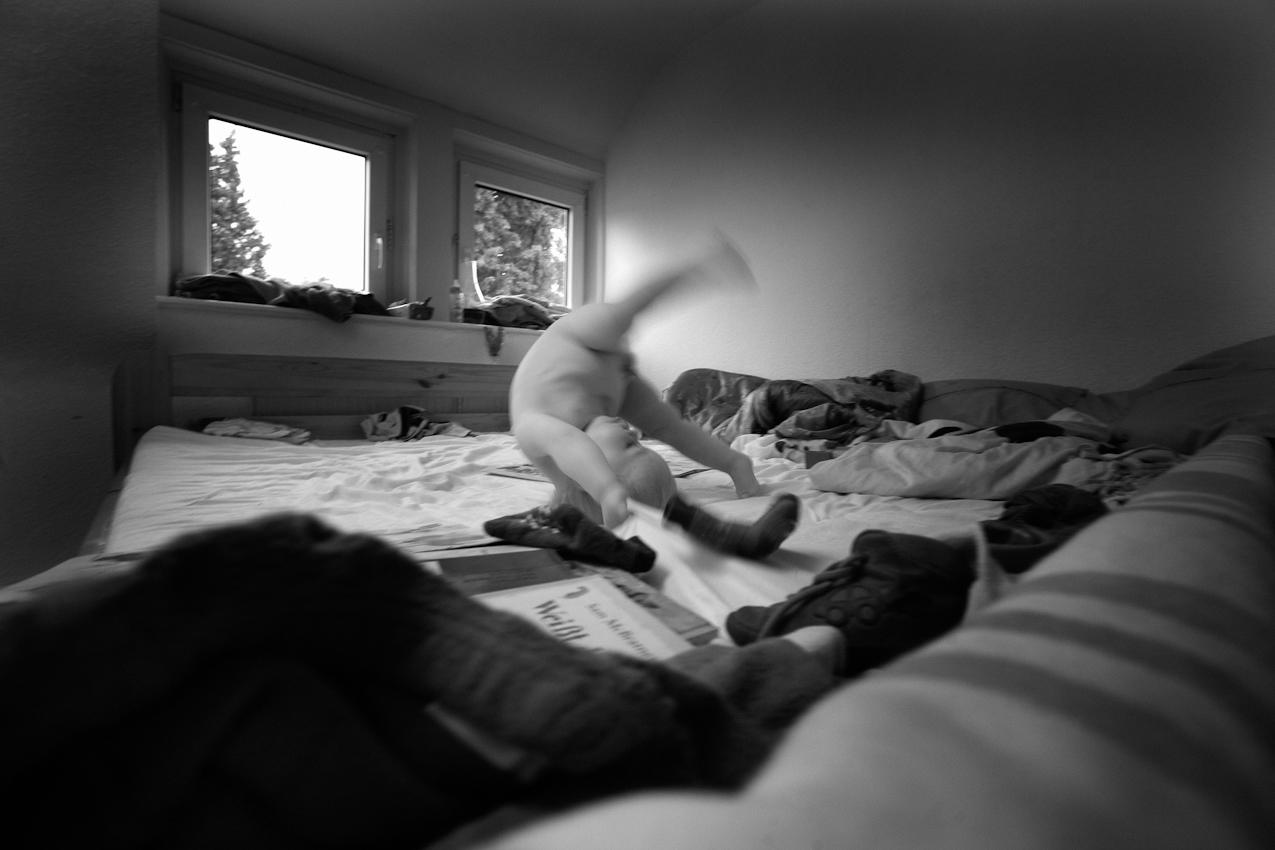 Elias gluckt im Bett seiner Eltern eine seiner ersten Rollen. ----- Titel:  Ganz bei sich -- Ein Tag im Leben von Elias Valentin Morascher; Sohn des Fotografen Arnold Morascher. Mein Hauptinteresse bestand darin, das Kind nicht in Interaktion mit anderen sondern in Konzentration auf sich selbst zu fotografieren. Die Serie zeigt die Eigenständigkeit des 18 Monate alten Kindes (geboren 14.11.2008),  die konzentrierten Momente. Lernen, Erfahren, Bewegung, selbständiges Spielen; auch die Frustration des Kindes, als es z.B. nicht in der Lage ist, alleine auf das Bett der Eltern zu klettern. Die Serie entstand in etwa vier Stunden zwischen 13:00 und 17:00 Uhr am 07.05.2010 und zeigt ein Stück Leben eines Kleinkindes in Deutschland /22175 Hamburg/Bramfeld.