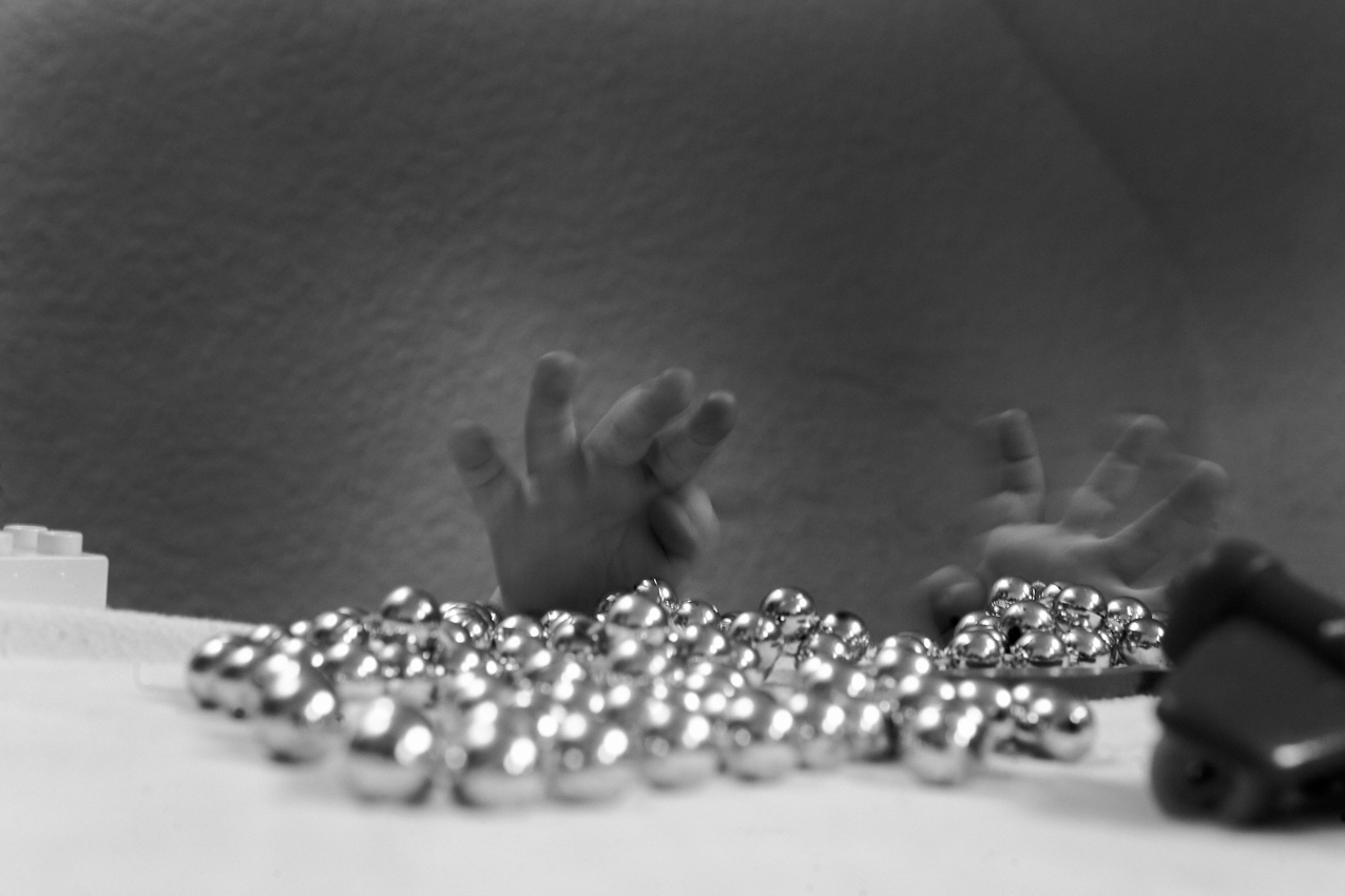 Elias Hände beim Spielen mit einer Plastikperlenkette. ----- Titel:  Ganz bei sich -- Ein Tag im Leben von Elias Valentin Morascher; Sohn des Fotografen Arnold Morascher. Mein Hauptinteresse bestand darin, das Kind nicht in Interaktion mit anderen sondern in Konzentration auf sich selbst zu fotografieren. Die Serie zeigt die Eigenständigkeit des 18 Monate alten Kindes (geboren 14.11.2008),  die konzentrierten Momente. Lernen, Erfahren, Bewegung, selbständiges Spielen; auch die Frustration des Kindes, als es z.B. nicht in der Lage ist, alleine auf das Bett der Eltern zu klettern. Die Serie entstand in etwa vier Stunden zwischen 13:00 und 17:00 Uhr am 07.05.2010 und zeigt ein Stück Leben eines Kleinkindes in Deutschland /22175 Hamburg/Bramfeld.