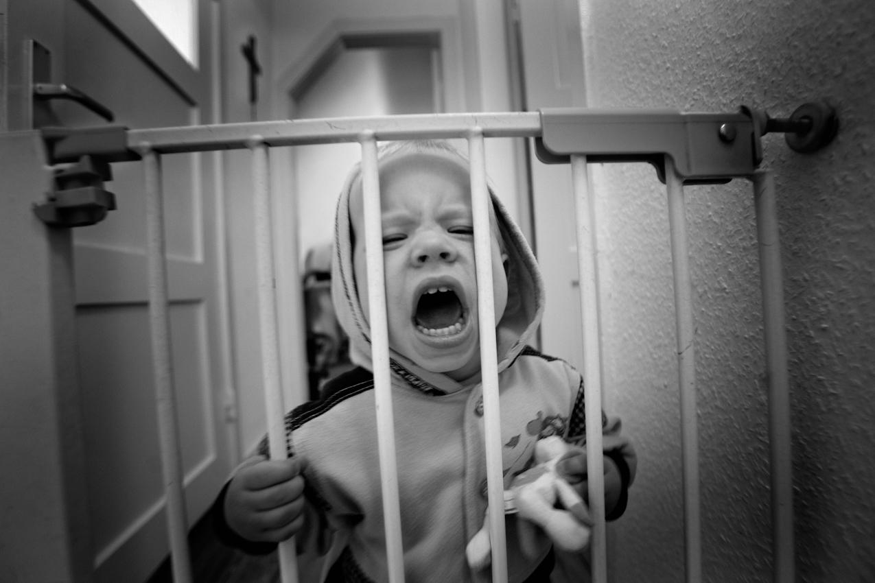 Elias ist wütend, weil er die Sicherheitstür zur Treppe nicht öffnen kann. ----- Titel:  Ganz bei sich -- Ein Tag im Leben von Elias Valentin Morascher; Sohn des Fotografen Arnold Morascher. Mein Hauptinteresse bestand darin, das Kind nicht in Interaktion mit anderen sondern in Konzentration auf sich selbst zu fotografieren. Die Serie zeigt die Eigenständigkeit des 18 Monate alten Kindes (geboren 14.11.2008),  die konzentrierten Momente. Lernen, Erfahren, Bewegung, selbständiges Spielen; auch die Frustration des Kindes, als es z.B. nicht in der Lage ist, alleine auf das Bett der Eltern zu klettern. Die Serie entstand in etwa vier Stunden zwischen 13:00 und 17:00 Uhr am 07.05.2010 und zeigt ein Stück Leben eines Kleinkindes in Deutschland /22175 Hamburg/Bramfeld.