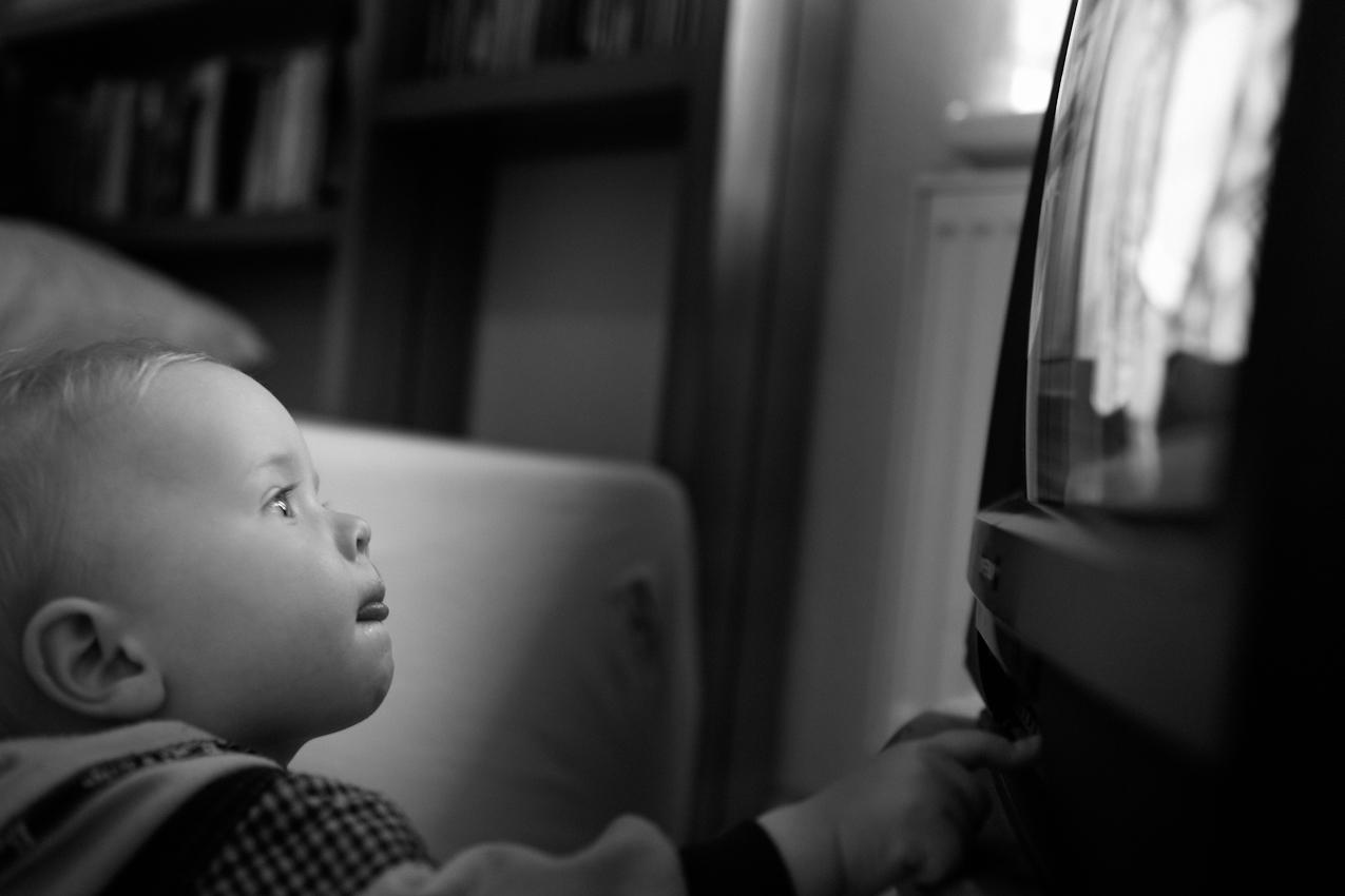 Elias konzentriert sich auf das Bild und das Drücken der Knöpfe am Fernseher. ---- Titel:  Ganz bei sich -- Ein Tag im Leben von Elias Valentin Morascher; Sohn des Fotografen Arnold Morascher. Mein Hauptinteresse bestand darin, das Kind nicht in Interaktion mit anderen sondern in Konzentration auf sich selbst zu fotografieren. Die Serie zeigt die Eigenständigkeit des 18 Monate alten Kindes (geboren 14.11.2008),  die konzentrierten Momente. Lernen, Erfahren, Bewegung, selbständiges Spielen; auch die Frustration des Kindes, als es z.B. nicht in der Lage ist, alleine auf das Bett der Eltern zu klettern. Die Serie entstand in etwa vier Stunden zwischen 13:00 und 17:00 Uhr am 07.05.2010 und zeigt ein Stück Leben eines Kleinkindes in Deutschland /22175 Hamburg/Bramfeld.