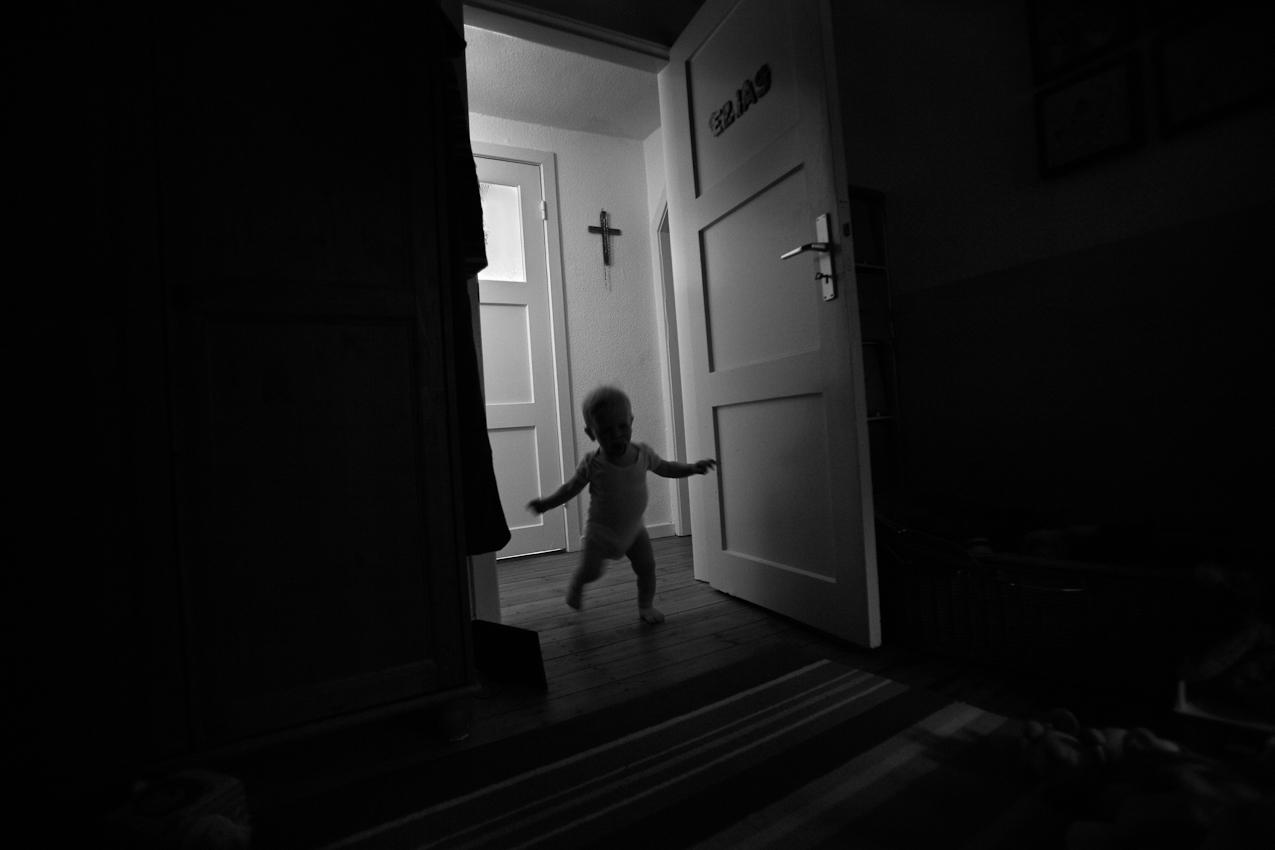 Elias läuft in sein Spielzimmer. Inzwischen erfordert Gehen und Laufen bei ihm nicht mehr so viel aktive Konzentration wie noch vor wenigen Wochen. ----- Titel:  Ganz bei sich -- Ein Tag im Leben von Elias Valentin Morascher; Sohn des Fotografen Arnold Morascher. Mein Hauptinteresse bestand darin, das Kind nicht in Interaktion mit anderen sondern in Konzentration auf sich selbst zu fotografieren. Die Serie zeigt die Eigenständigkeit des 18 Monate alten Kindes (geboren 14.11.2008),  die konzentrierten Momente. Lernen, Erfahren, Bewegung, selbständiges Spielen; auch die Frustration des Kindes, als es z.B. nicht in der Lage ist, alleine auf das Bett der Eltern zu klettern. Die Serie entstand in etwa vier Stunden zwischen 13:00 und 17:00 Uhr am 07.05.2010 und zeigt ein Stück Leben eines Kleinkindes in Deutschland /22175 Hamburg/Bramfeld.
