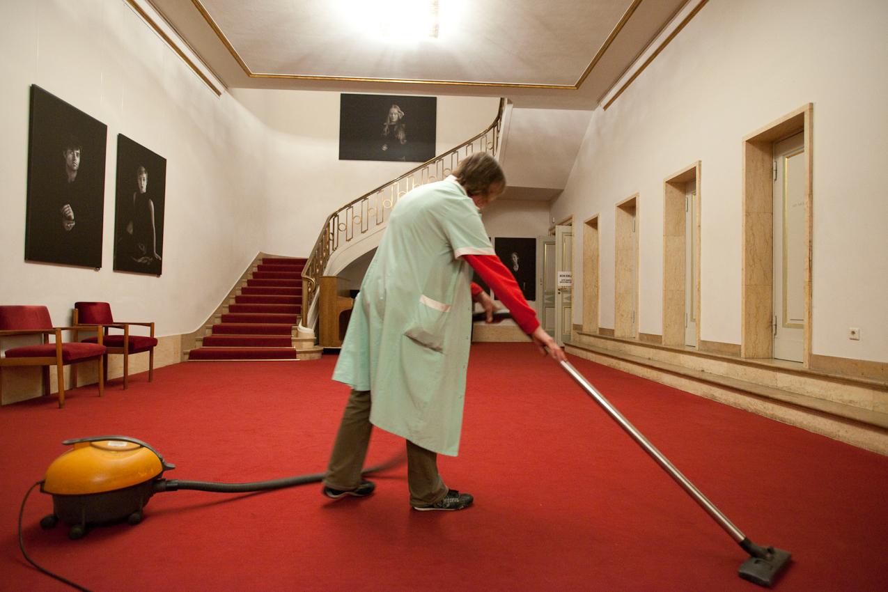Morgens saugt Raumpflegerin Heidi Wettlin das Foyer des Maxim Gorki Theaters Berlin. Im Hintergrund sind großformatige Fotos von Schauspielern des Theaters zu sehen.