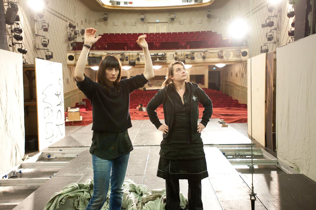 """Felicitas Brucker (Regisseurin, links) und Kathrin Frosch (Bühnenbildnerin) erklären den Bühnentechnikern, wie sie sich die Bühne für das kommende Stuck """"Penthesilea"""" vorstellen."""