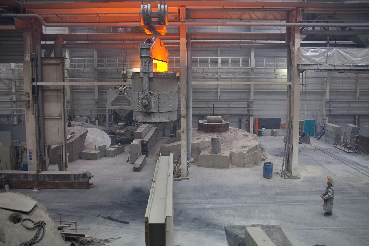 Ein Arbeiter fährt per Funksteuerung die Pfanne mit dem glühenden Gussmaterial zur Einfüllrinne.