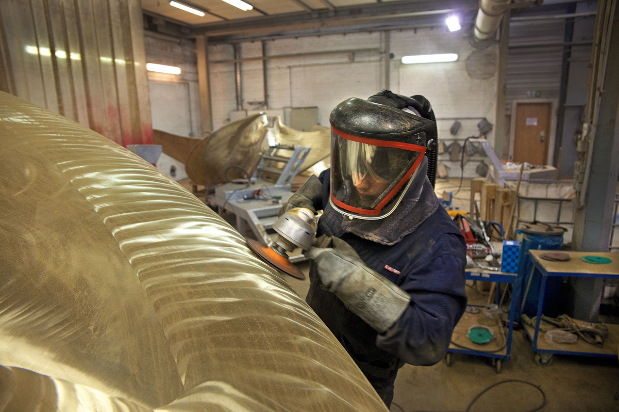 Schleifarbeiten an einem Propeller. Wegen der feinen Metallpigmente, die beim Schleifen durch die Luft wirbeln, ist der Schleifer mit einer Maske geschützt.