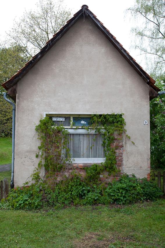 Weserbergland, Dielmissen, 12:49 Uhr. Eine frappierend einfache Giebelfassade, ein Fenster, das vielleicht mal Ladenfenster war, grünes Gerank. Ein ehemaliger Milchladen? Eine Wohngarage? Einziger Anhaltspunkt: die Hausnummer.