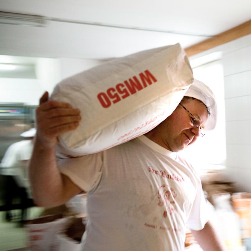 Bäckermeister Josef Salbaum aus dem fränkischen Städtchen Spalt schultert seine wohl wichtigste Zutat: Mehl.