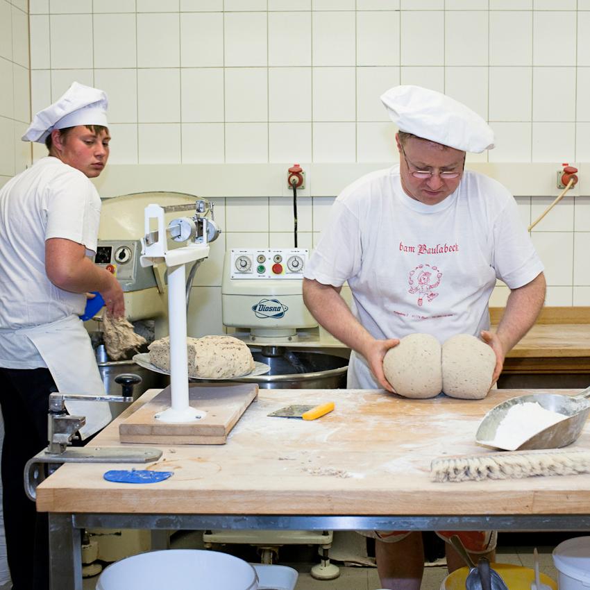 Während Lehrling Marco Wiedmann den herzhaften Brotteig zubereitet, formt Bäckermeister Josef Salbaum hingebungsvoll die Laibe.