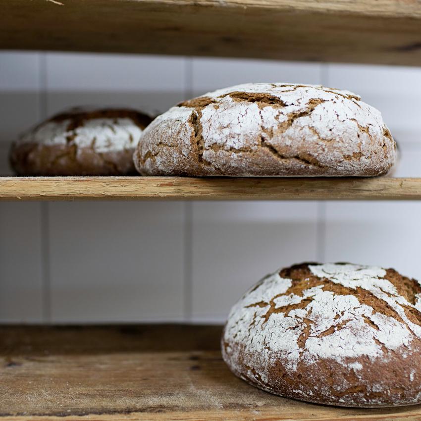 Die frischen, duftenden Brotlaibe kühlen auf Holzregalen ab.
