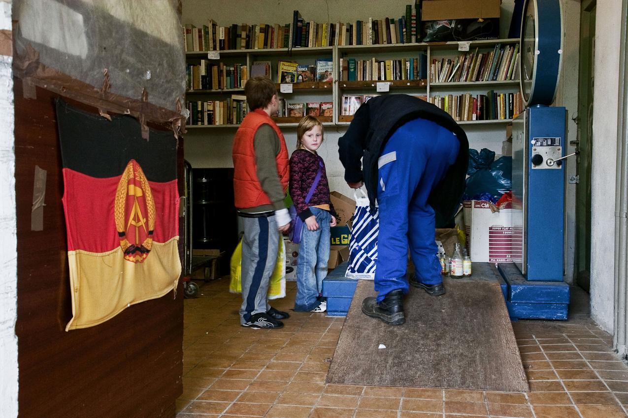 Bei Payperman, dem Altpapierprofi wird das Altglas der beiden Kinder auf einer Waage, die noch aus DDR-Bestand stammt, gewogen.