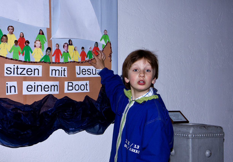 """In Vorbereitung seiner Erstkommunionsfeier, besucht Jakob Dicks,  am Nachmittag des 07.05.2010, die Pfarrkirche St. Peter in Krefeld-Uerdingen und steht vor dem selbstgebastelten Plakat, mit dem Motto """"Wir sitzten mit Jesus in einem Boot"""", der Kommunionskinder."""