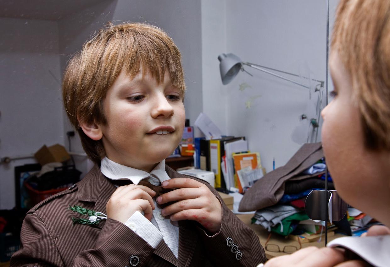 Am Nachmittag des 07.05.2010 im Haus der Familie Dicks in Krefeld. Jakob Dicks steht mit seinem Erstkommunionsanzug vor dem Spiegel im elterlichen Schlafzimmer und rueckt seine Fliege zurecht.