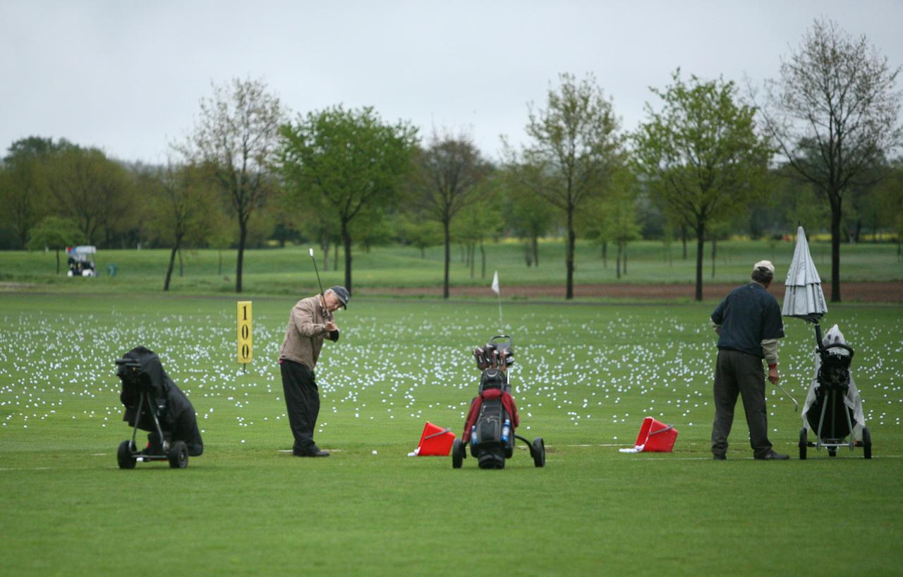 Auf der Drivingranch des Golfparks Heinhaus üben die Golfer Abschlage. Die vielen Bälle im Hintergrund zeugen von zahllosen Versuchen den perfekten Swing zu erreichen. Im Hintergrund links sieht man einen Greenkeeper bei der Arbeit. Mit einem fahrbaren Rasenmäher trimmt er den Rasen. Die Aufnahme wurde am 07.05.2010 um 11.54 gemacht.