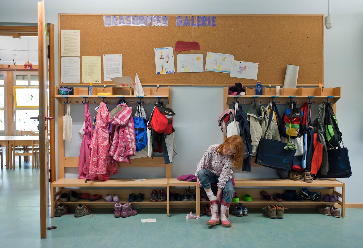 Bad Vilbel, DEU, 07.05.2010; Projekt Ein Tag Deutschland - An diesem Tag begleite ich meine Tochter Nike, 6 Jahre alt, in ihren Kindergarten Trauminsel. Die Kita ist Ende der Neunziger Jahre gebaut worden und sehr gut ausgestattet. Das Wohngebiet, in dem sich die Kita befindet, ist zur gleichen Zeit entstanden und besteht ueberwiegend aus Reihenhaeusern und einigen Mehrfamilienmietshaeusern. Es handelt sich hier um ein sehr kinderreiches Wohngebiet mit Familien aus ueberwiegend mittelstaendischen Einkommensverhaeltnissen. Zum Foto: Nike zieht sich Gummistiefel fuer das Spielen im Garten der Kita an. Heute darf etwas rumgematscht werden.