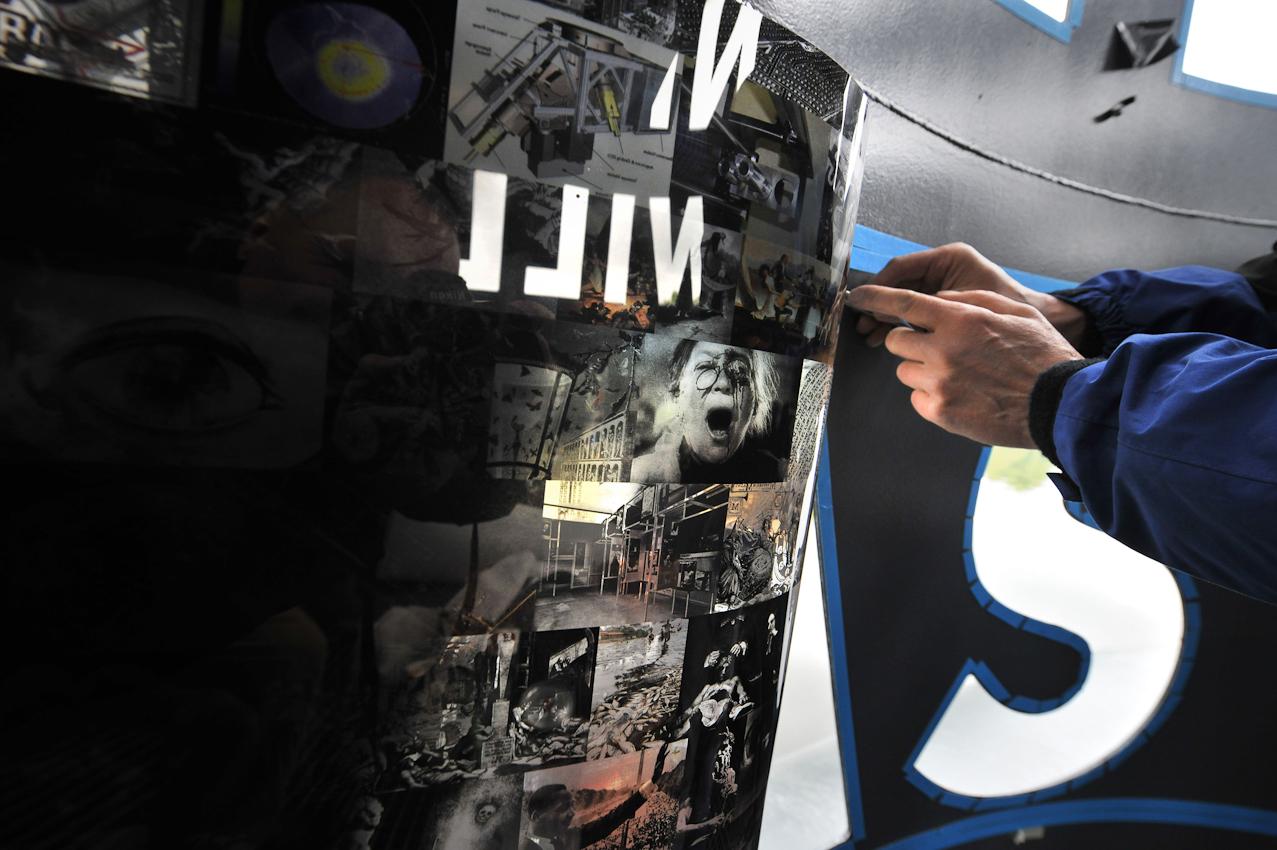 Am 7. Mai 2010 wird auf dem Baldeneysee in Essen/Ruhr an vier von insgesamt sechs Kunstinseln für das NRuhr-Atolli gebaut, Leuchtturmprojekt des Kulturhauptstadt-Programms der Ruhr.2010 GmbH. Günther Mühlhausen, Vertriebsleiter der Firma Grieger in Düsseldorf, installiert mit seinen Mitarbeitern Roman Domnisch und Christian Darius eine Bildcollage aus 8000 Fotos hinter die Cutouts im NU-Booti-Turm von Andreas M. Kaufmann und Hans Ulrich Reck. Detail: Roman Domnisch.