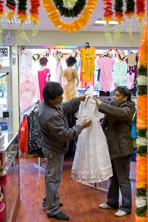 In ihrem Geschäft für Bollywood-Mode an der Vahrenwalderstraße in Hannover hängen die Inhaber ein Kleid wieder auf.