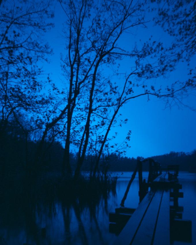 Das Bildmotiv zeigt einen Holzsteg am Pingsdorfer See im Zeitraum von 04h30 bis 05h45 am fruhen Morgen des 07. Mai 2010. Der See liegt im Naturschutzgebiet Villeseen in Bruhl am Wasserturmweg und Maiglerstra?e. Das Naturschutzgebiet Villenseen gehort zum Naturpark Rheinland und ist ein Naherholungsgebiet zwischen Koln und Bonn. Landschaft und Natur lasst sich im Naturpark Rheinland vielseitig erleben. Dort, wo noch bis vor kurzer Zeit Braunkohle abgebaut wurde, ist wieder eine okologisch wertvolle Landschaft entstanden. Heute konnen im Naturpark wieder seltene Tier- und Pflanzenarten beobachtet werden. Nach Beendigung des Braunkohlenabbaus entstand der Pingsdorfer See 1954 durch den langsamen Anstieg des Grundwassers. Der Pingsdorfer See mit 3,8 ha gro?en Flache steht unter Landschaftsschutz.Hier sind ganzjahrig geschutzte Laichzonen eingerichtet, die nicht betreten oder befischt werden durfen. Der See wird bewirtschaftet von einem ortsansassigen Angelverein. Um Abstand vom Arbeitsalltag, dem hohen Lebenstempo in einer Gro?stadt und dem oft ungesunden Umfeld durch Larm und schlechter Luft zu bekommen, geniesse ich schlicht und einfach in mitten der Natur die Stille. Durch die Entschleundigung des eigenen Lebens an dem ein oder anderen Tag komme ich zur Ruhe, durch die Entspannung breitet sich ein Gefuhl von Freiheit in mir aus. Durch das Festhalten und Darstellen von eben diesen einfachen Orten der Stille mochte ich simple jedoch lebenswichtige Inhalte uber intuitiv verstandliche Bildmotive transportieren. Wie in der vorliegenden Bildmotivreihe (Pingsdorfer See 01, 02 und 03) verbringe ich aus diesem Grund auch gerne einen gesamten Tag vor Ort; - mit dem Beginn der ersten Aufnahme noch vor dem Sonnenaufgang und der letzten Belichtung des Tages bis nach dem Sonnenuntergang. Die Unterschiede liegen sehr oft lediglich im Detail. Allerdings gibt es auch Tage, da verandern sich Orte und demnach auch die Bildmotivsequenzen grundlegend, scheinen nicht mehr zusammenzupassen