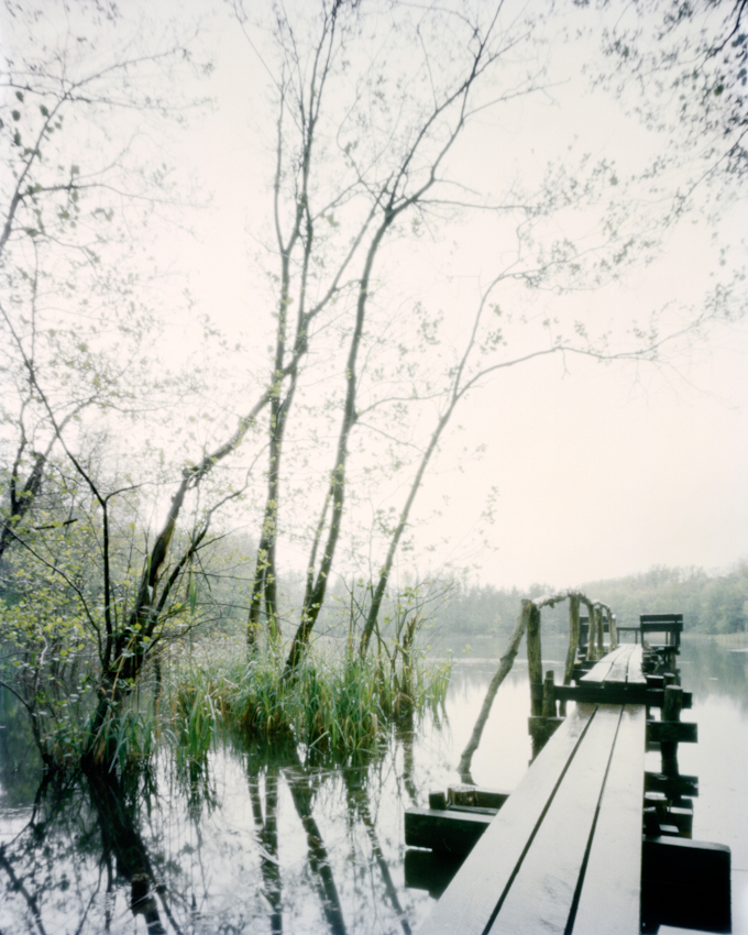 Das Bildmotiv zeigt einen Holzsteg am Pingsdorfer See im Zeitraum von 17h30 bis 18h45 am spaten Nachmittag des 07. Mai 2010.Der See liegt im Naturschutzgebiet Villeseen in Bruhl am Wasserturmweg und Maiglerstra?e.Das Naturschutzgebiet Villenseen gehort zum Naturpark Rheinland und ist ein Naherholungsgebiet zwischen Koln und Bonn.Landschaft und Natur lasst sich im Naturpark Rheinland vielseitig erleben.Dort, wo noch bis vor kurzer Zeit Braunkohle abgebaut wurde, ist wieder eine okologisch wertvolle Landschaft entstanden.Heute konnen im Naturpark wieder seltene Tier- und Pflanzenarten beobachtet werden.Nach Beendigung des Braunkohlenabbaus entstand der Pingsdorfer See 1954 durch den langsamen Anstieg des Grundwassers.Der Pingsdorfer See mit 3,8 ha gro?en Flache steht unter Landschaftsschutz.Hier sind ganzjahrig geschutzte Laichzonen eingerichtet, die nicht betreten oder befischt werden durfen.Der See wird bewirtschaftet von einem ortsansassigen Angelverein.Um Abstand vom Arbeitsalltag, dem hohen Lebenstempo in einer Gro?stadt und dem oft ungesunden Umfeld durch Larm und schlechter Luft zu bekommen, geniesse ich schlicht und einfach in mitten der Natur die Stille.Durch die Entschleundigung des eigenen Lebens an dem ein oder anderen Tag komme ich zur Ruhe, durch die Entspannung breitet sich ein Gefuhl von Freiheit in mir aus.Durch das Festhalten und Darstellen von eben diesen einfachen Orten der Stille mochte ich simple jedoch lebenswichtige Inhalte uber intuitiv verstandliche Bildmotive transportieren.Wie in der vorliegenden Bildmotivreihe (Pingsdorfer See 01, 02 und 03) verbringe ich aus diesem Grund auch gerne einen gesamten Tag vor Ort; - mit dem Beginn der ersten Aufnahme noch vor dem Sonnenaufgang und der letzten Belichtung des Tages bis nach dem Sonnenuntergang. Die Unterschiede liegen sehr oft lediglich im Detail. Allerdings gibt es auch Tage, da verandern sich Orte und demnach auch die Bildmotivsequenzen grundlegend, scheinen nicht mehr zusammenzupassen - noch 