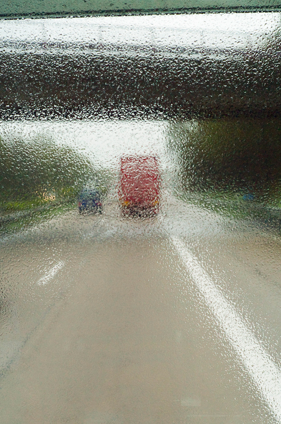 Ein Tag durch Deutschland: im Schnelldurchlauf in 8 Stunden trampenderweise von Hamburg zum Bodensee entlang der A7, der langsten deutschen Autobahn. Beginn der Reise im Nieselregen, Blick aus der Lastwagenwindschutzscheibe auf die Fahrbahn nahe Hamburg.