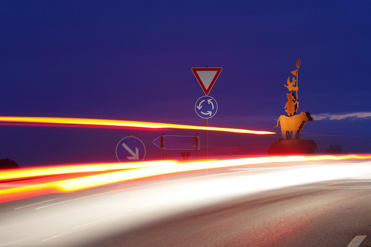 """Am Ortseingang zu Kressbronn auf dem songenannten, """"Aral-Kreisel, (nach der nahen Araltankstelle), an der Auffahrt von der Landesstraße L334 auf die Bundesstraße B 31 (Linderhof), befindet sich seit 2006 eine Stahlskulptur, die das bäuerliche Leben leicht ironisch darstellt."""