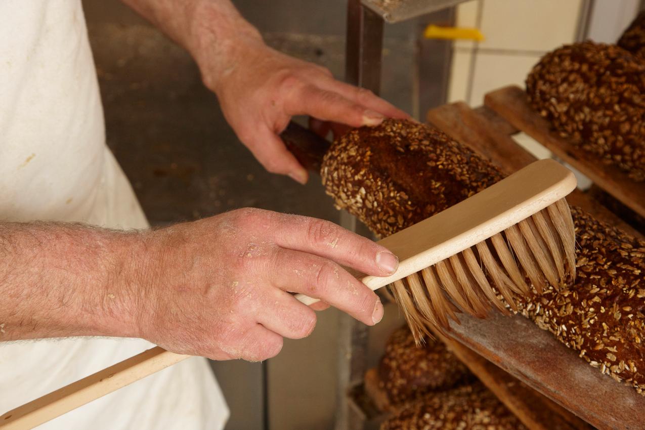 Gleich nachdem Bäckermeister Jens Afheldt (47) aus Reinfeld einen Schwung Brote aus dem Ofen geholt hat, werden diese mit einem weichen, in Wasser getauchten Streicher abgepinselt, damit die Brotkruste schon glänzend und knusprig wird.