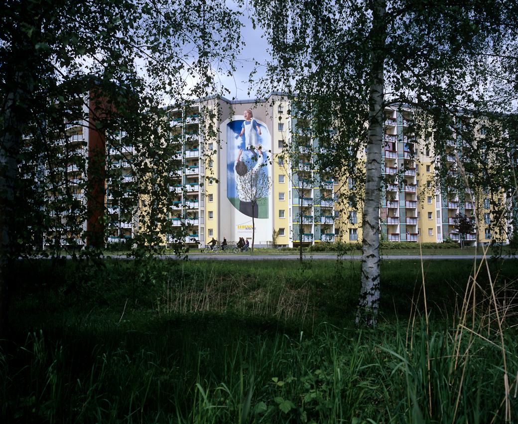DEU, Deutschland, Germany, Hoyerswerda, Sachsen, 07.05.2010 Wandmalerei an renovierten Hochhaeusern im Plattenbaustil der Lebensraeume eG im Wohnkomplex V in Hoyerswerda-Neustadt. Aus der Serie ' Hoyerswerda - Die Schrumpfende Stadt '. Hoyerswerda-Neustadt mit seinen zehn Wohnkomplexen WK I-X war einst die sozialistische Vorzeigemetropole der DDR. Gekennzeichnet durch die in industrieller Bauweise gefertigten gleichfoermigen Plattenbauten galt es als Modell fuer eine funktionale Stadt der Moderne. Gut Zwanzig Jahre nach dem Mauerfall, ist Hoyerswerda die am staerksten schrumpfende Stadt in Deutschland.