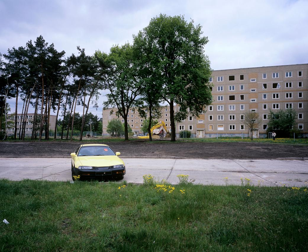 DEU, Deutschland, Germany, Hoyerswerda, Sachsen, 07.05.2010 Verlassenes Auto und Bagger vor Leerstehenden Plattenbauten kurz vor dem Abriss im Wohnkomplex X in Hoyerswerda-Neustadt. Aus der Serie ' Hoyerswerda - Die Schrumpfende Stadt '. Hoyerswerda-Neustadt mit seinen zehn Wohnkomplexen WK I-X war einst die sozialistische Vorzeigemetropole der DDR. Gekennzeichnet durch die in industrieller Bauweise gefertigten gleichfoermigen Plattenbauten galt es als Modell fuer eine funktionale Stadt der Moderne. Gut Zwanzig Jahre nach dem Mauerfall, ist Hoyerswerda die am staerksten schrumpfende Stadt in Deutschland.