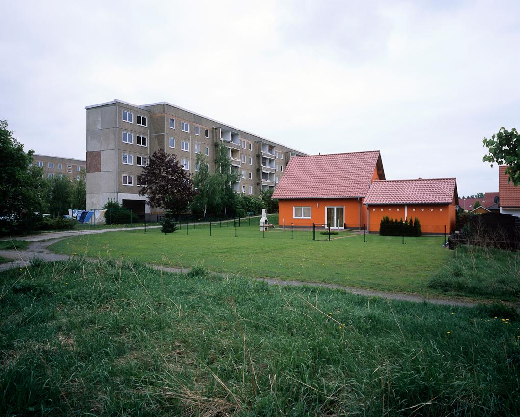DEU, Deutschland, Germany, Hoyerswerda, Sachsen, 07.05.2010 Ein dem Abriss preisgegebener Plattenbau und eine neue Einfamiliensiedlung im Wohnkomplex X in Hoyerswerda-Neustadt. Aus der Serie ' Hoyerswerda - Die Schrumpfende Stadt '. Hoyerswerda-Neustadt mit seinen zehn Wohnkomplexen WK I-X war einst die sozialistische Vorzeigemetropole der DDR. Gekennzeichnet durch die in industrieller Bauweise gefertigten gleichfoermigen Plattenbauten galt es als Modell fuer eine funktionale Stadt der Moderne. Gut Zwanzig Jahre nach dem Mauerfall, ist Hoyerswerda die am staerksten schrumpfende Stadt in Deutschland.